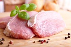 Côtelettes de porc crues sur le panneau de découpage Photo stock