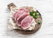 Côtelettes de porc crues sur une planche à découper en bois rustique Photos libres de droits