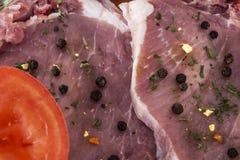 Côtelettes de porc crues, tomate et plan rapproché d'épices Photographie stock libre de droits