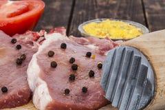 Côtelettes de porc et un plan rapproché de marteau de viande Image stock
