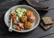 Côtelettes de poulet et salade de légume frais de plat en céramique sur le fond en bois foncé Images stock