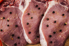 Côtelettes et épices de porc sur un conseil en bois Images stock