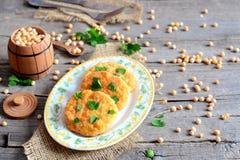 Côtelettes frites de pois d'un plat Les côtelettes végétariennes saines cuites du jaune ont séché des pois et décorentes du persi Photo libre de droits