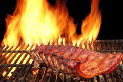 Côtes de découvert de porc de BBQ sur le gril flamboyant chaud Photos stock