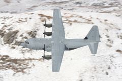 C130 Hercules and snow. A C130 Hercules flys low against a snowy backdrop in Wales on a training sortie stock image