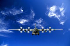 C130 Military airplane. Front view over a cloudy blue sky Royalty Free Stock Photo