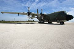 C130 on the runway. C130 military ariplane parked on a runway against a blue sky with wite coulds Royalty Free Stock Photography