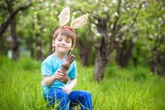 Caça do rapaz pequeno para o ovo da páscoa no jardim da mola no dia cute Imagem de Stock