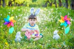Caça do rapaz pequeno para o ovo da páscoa no jardim da mola no dia da Páscoa Criança pequena bonito com coelho tradicional que c imagem de stock