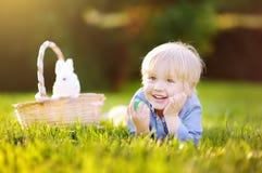 Caça encantador do rapaz pequeno para o ovo da páscoa no parque da mola no dia da Páscoa Imagens de Stock Royalty Free