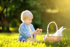 Caça encantador do rapaz pequeno para o ovo da páscoa no parque da mola no dia da Páscoa Fotografia de Stock Royalty Free