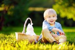 Caça encantador do rapaz pequeno para o ovo da páscoa no parque da mola no dia da Páscoa Imagem de Stock Royalty Free