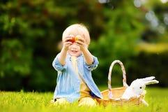 Caça encantador do rapaz pequeno para o ovo da páscoa no parque da mola no dia da Páscoa Fotos de Stock Royalty Free