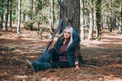 Caçador bonito da mulher na floresta com arma Imagem de Stock