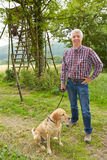 Caçador com o cão na frente do suporte da árvore Foto de Stock