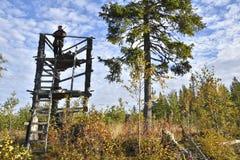 Caçador dos alces em uma torre da caça que guarda seu rifle foto de stock royalty free