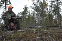 Caçador dos alces que senta-se em um coto que guarda seu rifle fotografia de stock royalty free