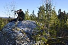 Caçador dos alces que senta-se em uma pedra grande que aponta com um rifle fotografia de stock