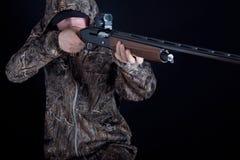 Caçador na roupa da camuflagem com uma arma em um fundo preto isolado O homem com a espingarda Indivíduo novo em um terno do camo imagens de stock royalty free