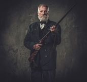 Caçador superior com uma espingarda em uma roupa tradicional do tiro, levantando em um fundo escuro Imagens de Stock Royalty Free