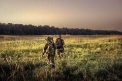 Caçadores com caça do equipamento que atravessa afastado o campo rural para a floresta no por do sol durante a época de caça no c fotos de stock