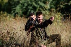 Caçadores com os rifles no ambiente da natureza Guardas florestais dos caçadores que procuram o animal ou o pássaro Caça com amig foto de stock royalty free
