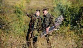 Caçadores com os rifles no ambiente da natureza Sócio do caçador furtivo - em - crime Atividade para o conceito real dos homens G imagens de stock