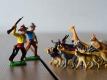 Caçadores contra animais selvagens Figuras plásticas diminutas FO macias imagens de stock