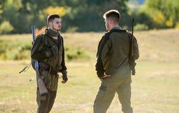 Caçadores do homem com arma do rifle Boot Camp Amizade de caçadores dos homens Forças do exército camuflar Forma uniforme militar fotos de stock royalty free