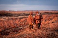 Caçadores que olham para fora para a rapina durante a caça no campo rural durante o nascer do sol foto de stock royalty free