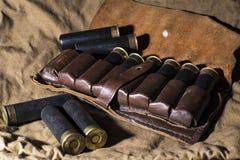 Caçando ainda a vida, correia de cartucho do caçador com shell de espingarda imagens de stock royalty free