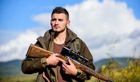 Caçando o equipamento e as medidas de segurança Homem com fundo da natureza do equipamento da caça do rifle Certifique-se da cond fotos de stock