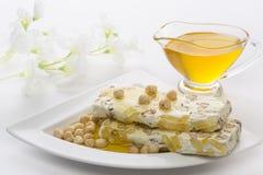 A caçarola com mel e nougat com porcas molhou o mel Imagem de Stock