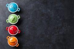 Caçarolas coloridas na tabela de pedra foto de stock