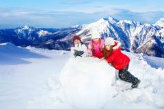 Caçoa balling acima da bola de neve enorme que faz um boneco de neve Fotos de Stock Royalty Free