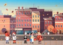 Caçoa desenhos animados felizes de passeio vestindo do Dia das Bruxas das doçuras ou travessura do fundo da arquitetura da cidade ilustração stock