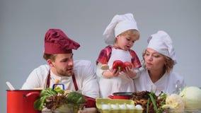 Caçoa o dia feliz do enyoj O rapaz pequeno bonito e seus pais bonitos estão sorrindo ao cozinhar na cozinha Família nova vídeos de arquivo