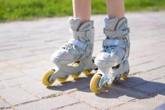 Caçoa os pés em patins de rolo - lazer, infância, jogos exteriores e conceito do esporte imagens de stock royalty free