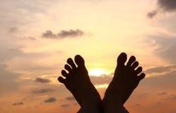 Caçoa a silhueta dos pés no fundo do por do sol Foto de Stock Royalty Free