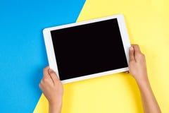 Caçoe as mãos com o tablet pc no fundo azul e amarelo imagem de stock royalty free