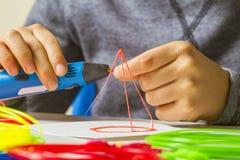 Caçoe as mãos com a pena 3d, filamentos coloridos na mesa branca Foto de Stock