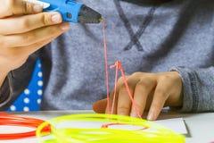 Caçoe as mãos com a pena da impressão 3d, filamentos coloridos na mesa branca Fotografia de Stock Royalty Free