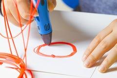 Caçoe as mãos com a pena da impressão 3d, filamentos coloridos na mesa branca Imagem de Stock