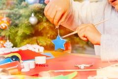 Caçoe as mãos do ` s com ornamento e pincel do Natal fotos de stock