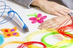 Caçoe as mãos e a pena da impressão 3d, filamentos coloridos na mesa branca Foto de Stock