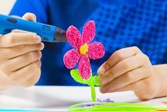 Caçoe as mãos que criam com a pena azul da impressão 3d Imagens de Stock Royalty Free