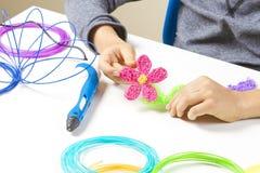 Caçoe as mãos que criam com a pena 3d, filamentos coloridos na mesa branca Foto de Stock