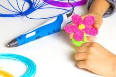 Caçoe as mãos que criam com a pena da impressão 3d, filamentos coloridos na mesa branca Foto de Stock Royalty Free