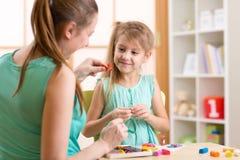 Caçoe brinquedos coloridos da argila do jogo da menina e da mãe em Foto de Stock Royalty Free