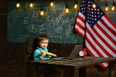 Caçoe com o computador na escola primária no fundo da bandeira nacional dos EUA Aluno no fundo com a bandeira dos EUA foto de stock royalty free